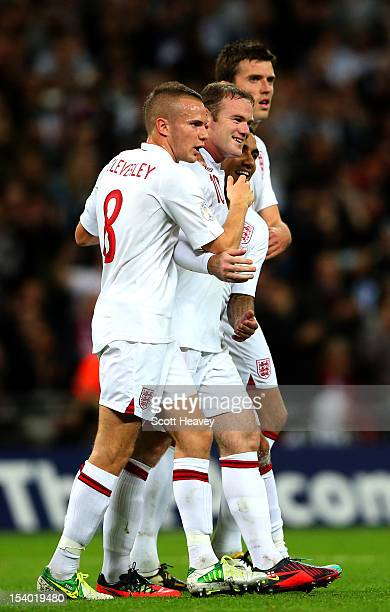 Wayne Rooney captain of England celebrates with team-mates Tom Cleverley, Aaron Lennon and Michael Carrick after scoring the opening goal from the...