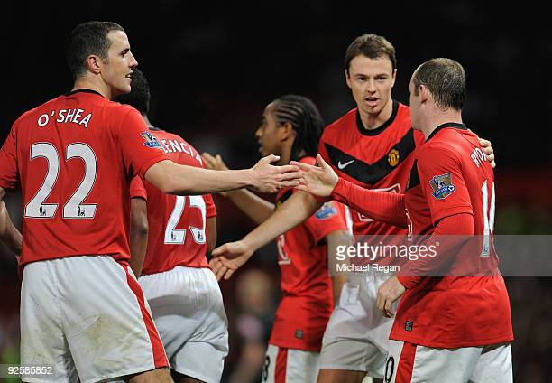 Wayne Rooney celebrates his goal with team mates John O'Shea and Jonny Evans during the Barclays Premier League match between Manchester United and...