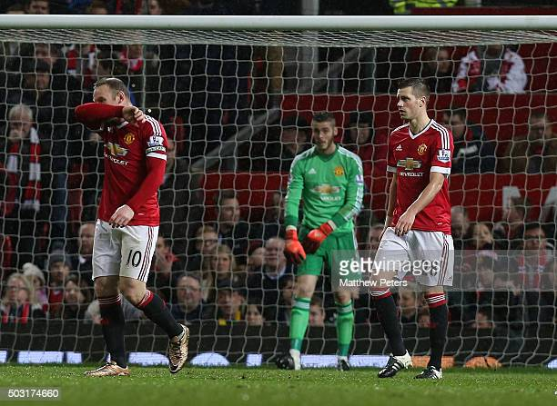 Wayne Rooney David de Gea and Morgan Schneiderlin of Manchester United show their disappointment at conceding a goal to Gylfi Sigurdsson of Swansea...