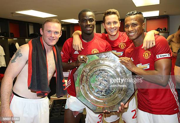 Wayne Rooney, Eric Bailly, Ander Herrera and Antonio Valencia of Manchester United pose with the Community Shield trophy in the dressing room after...