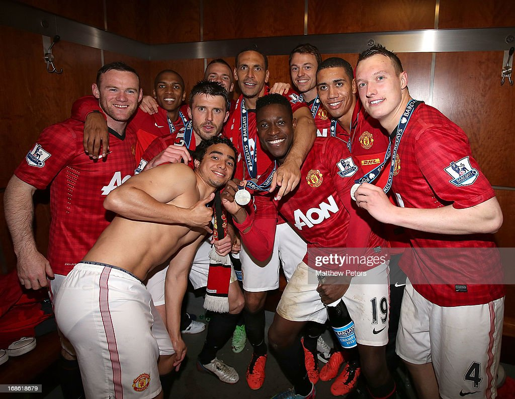 Wayne Rooney, Michael Carrick, Rafael da Silva, Danny Welbeck, Rio Ferdinand, Chris Smalling and Phil Jones of Manchester United celebrates with the Barclays Premier League trophy in the dressing room after the Barclays Premier League match between Manchester United and Swansea City at Old Trafford on May 12, 2013 in Manchester, England.