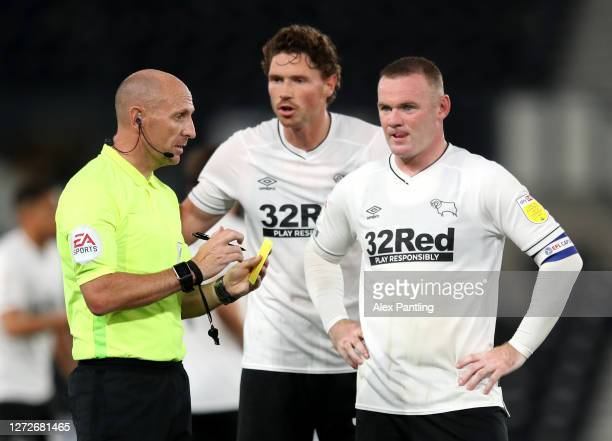Wayne Rooney of Derby chats with the match referee Andy Davies during the Carabao Cup Second Round match between Derby County and Preston North End...