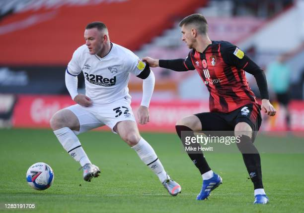 Wayne Rooney of Derby County is challenged by Chris Mepham of AFC Bournemouth during the Sky Bet Championship match between AFC Bournemouth and Derby...