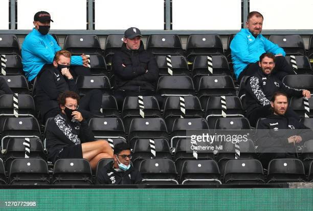 Wayne Rooney of Derby County sits with team mates in the stands during the Carabao Cup First Round match between Derby County and Barrow at Pride...