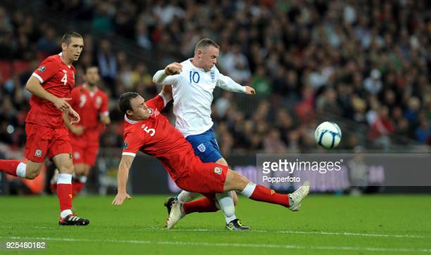 Wayne Rooney of England and Darcy Blake of Wales battle for the ball during the UEFA EURO 2012 group G qualifying match between England and Wales at...