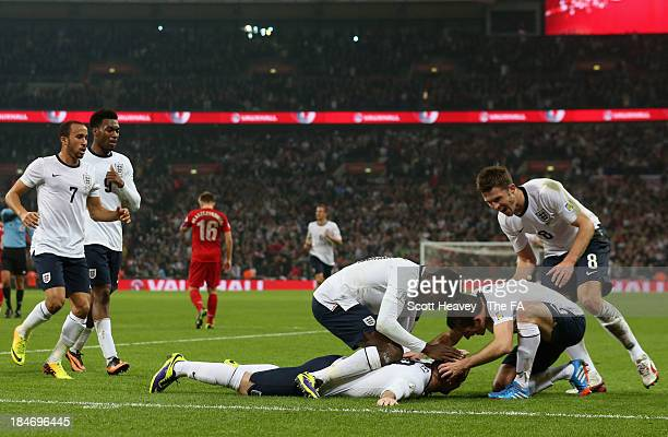 Wayne Rooney of England celebrates scoring their first goal with Danny Welbeck, Leighton Baines and Michael Carrick of England during the FIFA 2014...