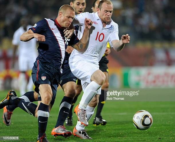 Wayne Rooney of England clashes with Jay DeMerit of the USA during the 2010 FIFA World Cup South Africa Group C match between England and USA at the...