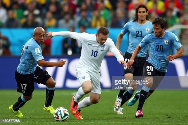 Wayne Rooney of England controls the ball against Egidio Arevalo Rios and Alvaro Gonzalez of Uruguay during the 2014 FIFA World Cup Brazil Group D...