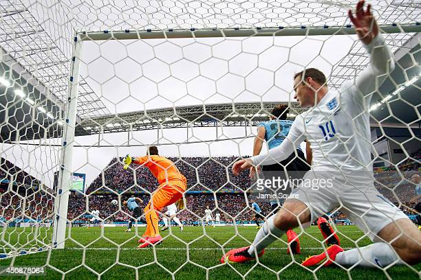 Wayne Rooney of England falls into the net after his header went off the crossbar against goalkeeper Fernando Muslera of Uruguay during the 2014 FIFA...