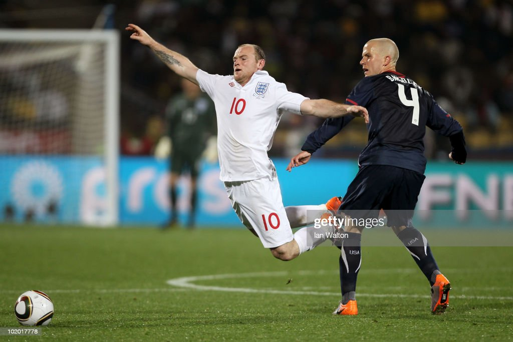 Wayne Rooney of England falls to the ground after a challenge by Michael Bradley of the United States during the 2010 FIFA World Cup South Africa Group C match between England and USA at the Royal Bafokeng Stadium on June 12, 2010 in Rustenburg, South Africa.