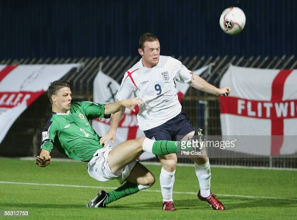 Wayne Rooney of England gets tackled by Chris Baird of Northern Ireland during a World Cup Qualifier Group six match at Windsor Park on September 7...