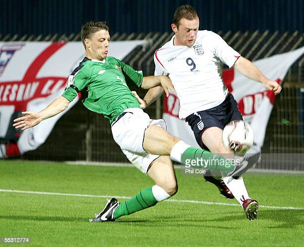 Wayne Rooney of England gets tackled by Chris Baird of Northern Ireland during the World Cup Qualifier Group six match at Windsor Park on September 7...