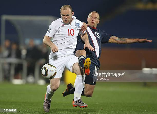 Wayne Rooney of England holds off a challenge from Jay Demerit of the United States during the 2010 FIFA World Cup South Africa Group C match between...