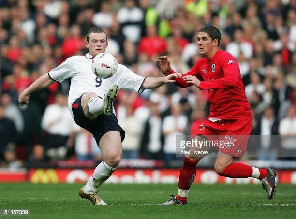 Wayne Rooney of England holds off Carl Robinson of Wales during the 2006 World Cup Qualifying match between England and Wales at Old Trafford on...