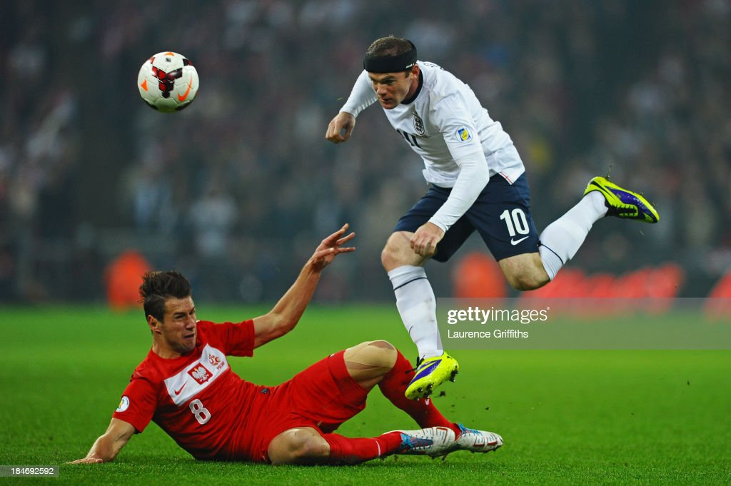 Wayne Rooney of England hurdles the challenge from Grzegorz Krychowiak of Poland during the FIFA 2014 World Cup Qualifying Group H match between England and Poland at Wembley Stadium on October 15, 2013 in London, England.