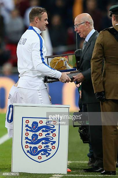 Wayne Rooney of England is awarded his 100th cap by Sir Bobby Charlton prior to the EURO 2016 Qualifier Group E match between England and Slovenia at...