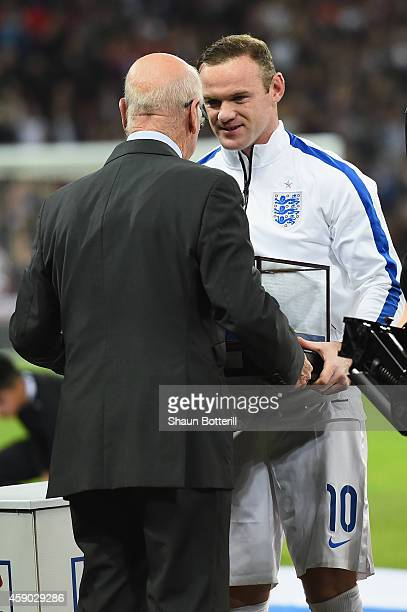 Wayne Rooney of England is awarded his 100th cap by Sir Bobby Charlton prior to during the EURO 2016 Qualifier Group E match between England and...