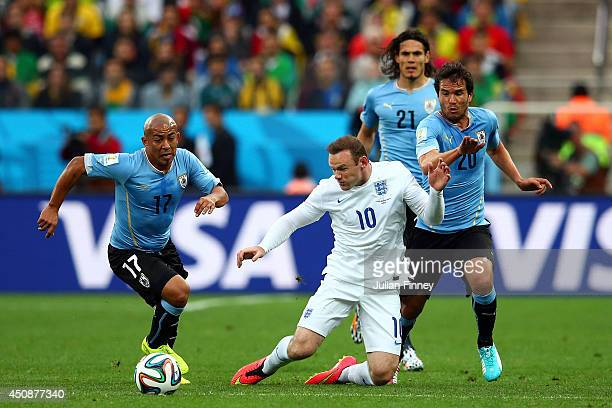 Wayne Rooney of England is challenged by Egidio Arevalo Rios and Alvaro Gonzalez of Uruguay during the 2014 FIFA World Cup Brazil Group D match...