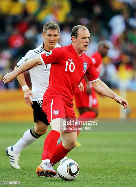 Wayne Rooney of England is chased by Bastian Schweinsteiger of Germany during the 2010 FIFA World Cup South Africa Round of Sixteen match between...