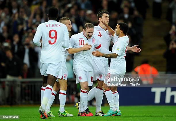 Wayne Rooney of England is congratulated by teammates after scoring the opening goal from the penalty spot during the FIFA 2014 World Cup Group H...
