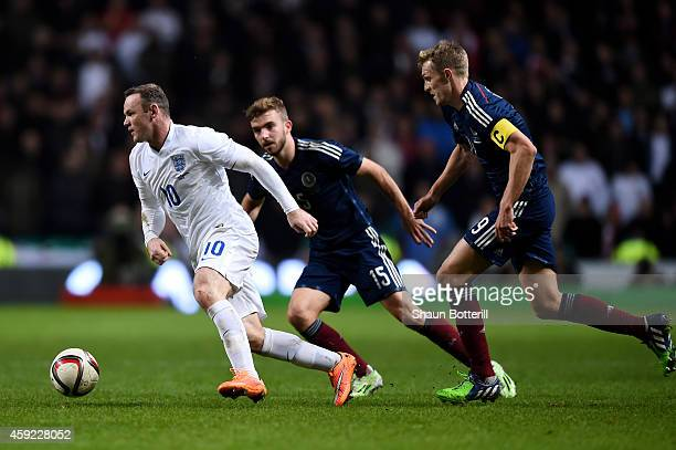 Wayne Rooney of England is pursued by James Morrison of Scotland and Chris Martin of Scotland during the International Friendly match between...