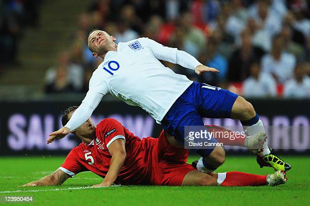 Wayne Rooney of England is tackled by Darcy Blake of Wales during the UEFA EURO 2012 group G qualifying match between England and Wales at Wembley...