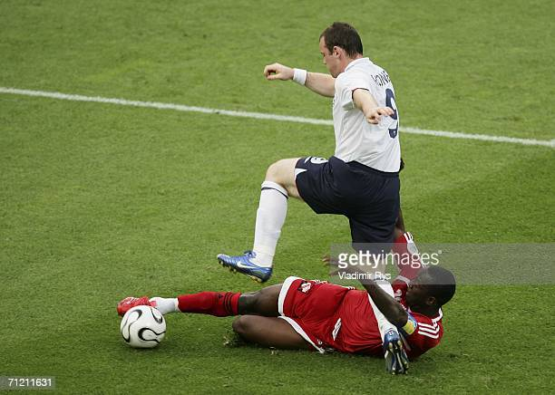 Wayne Rooney of England is tackled by Dwight Yorke of Trinidad and Tobago during the FIFA World Cup Germany 2006 Group B match between England and...