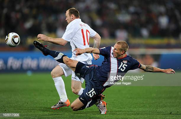 Wayne Rooney of England is tackled by Jay Demerit of the United States during the 2010 FIFA World Cup South Africa Group C match between England and...