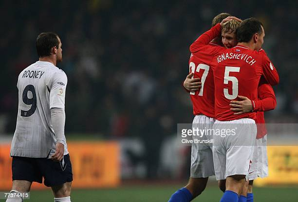 Wayne Rooney of England leaves the pitch as Russian goal scorer Roman Pavlyuchenko celebrates at the final whistle during the Euro 2008 Qualifying...