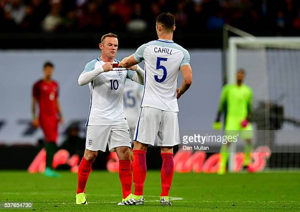 Wayne Rooney of England passes the captain's armband to Gary Cahill during the international friendly match between England and Portugal at Wembley...