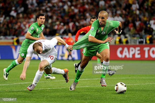 Wayne Rooney of England pulls the jersey of Madjid Bougherra of Algeria during the 2010 FIFA World Cup South Africa Group C match between England and...