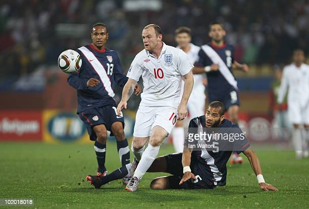 Wayne Rooney of England rides the tackle by Oguchi Onyewu of the United States during the 2010 FIFA World Cup South Africa Group C match between...