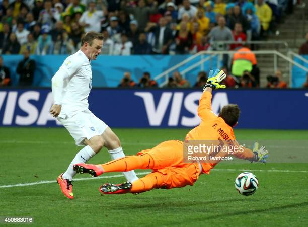 Wayne Rooney of England scores his team's first goal past Fernando Muslera of Uruguay during the 2014 FIFA World Cup Brazil Group D match between...