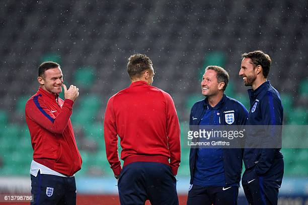 Wayne Rooney of England smiles as he speaks with Interim Manager Gareth Southgate firstteam coach Steve Holland and Jamie Vardy during a tour of the...