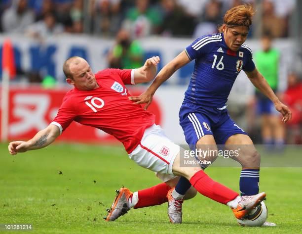 Wayne Rooney of England tackles Yoshito Okubo of Japan during the International Friendly between Japan and England at UPC-Arena on May 30, 2010 in...