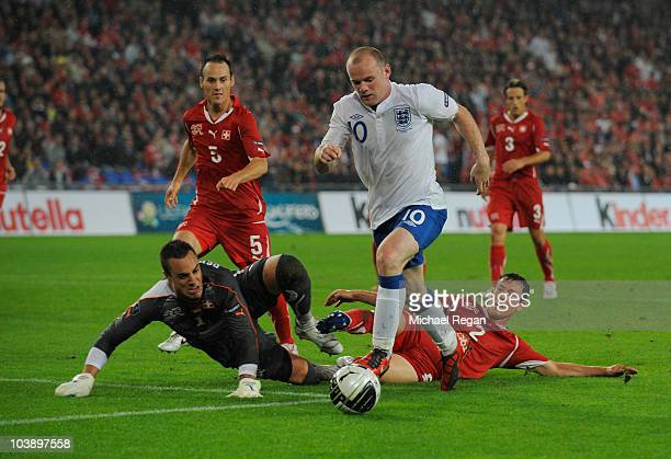 Wayne Rooney of England takes on Stephan Lichtsteiner Steve von Bergen and Diego Benaglio of Switzerland during the EURO 2012 Group G Qualifier...
