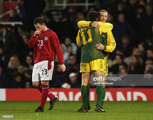 Wayne Rooney of England walks away dejected as Stan Lazaridis and Craig Moore of Australia celebrate a third goal during the International Friendly...