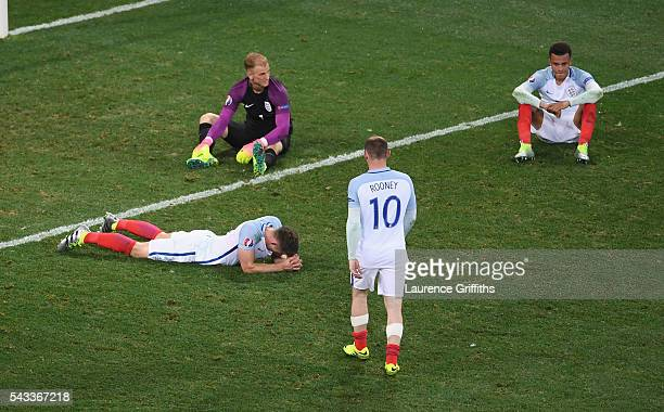 Wayne Rooney of England walks to console Gary Cahill , Joe Hart and Dele Alli after their defeat in the UEFA EURO 2016 round of 16 match between...