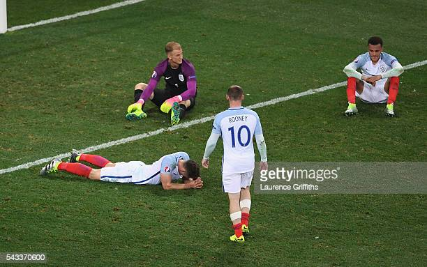 Wayne Rooney of England walks to console Gary Cahill Joe Hart and Dele Alli after their defeat in the UEFA EURO 2016 round of 16 match between...