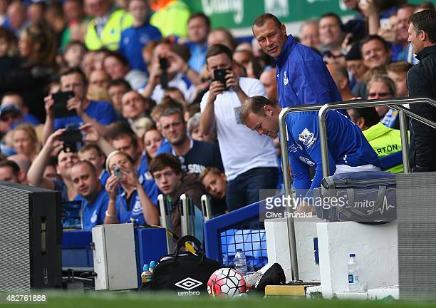 Wayne Rooney of Everton and Manchester United is watched closely by Duncan Ferguson before running on to the pitch to replace Tom Cleverley of...