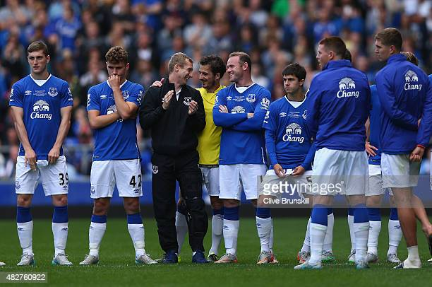 Wayne Rooney of Everton and Manchester United shares a joke Tony Hibbert of Everton at the end of the Duncan Ferguson Testimonial match between...