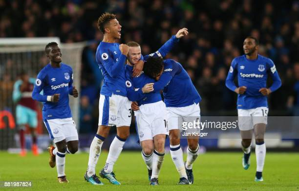 Wayne Rooney of Everton celebrates after scoring his sides third goal with Mason Holgate of Everton and Ashley Williams of Everton during the Premier...