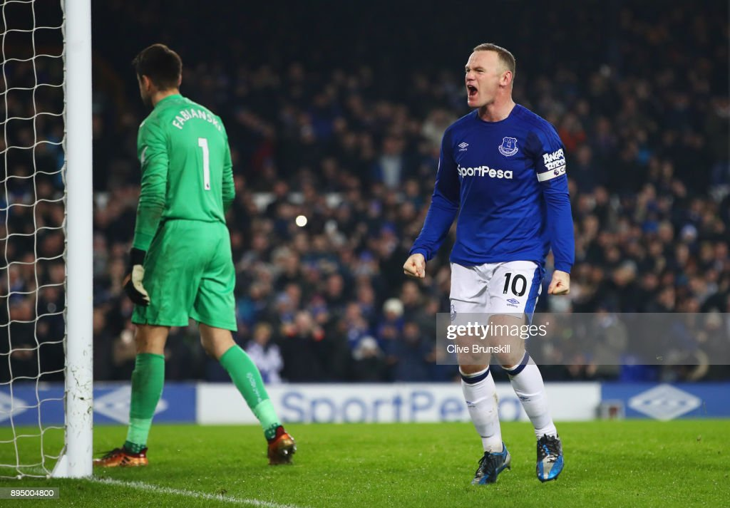 Wayne Rooney of Everton celebrates as he scores their third goal from the penalty spot as Lukasz Fabianski of Swansea City (1) looks dejected during the Premier League match between Everton and Swansea City at Goodison Park on December 18, 2017 in Liverpool, England.