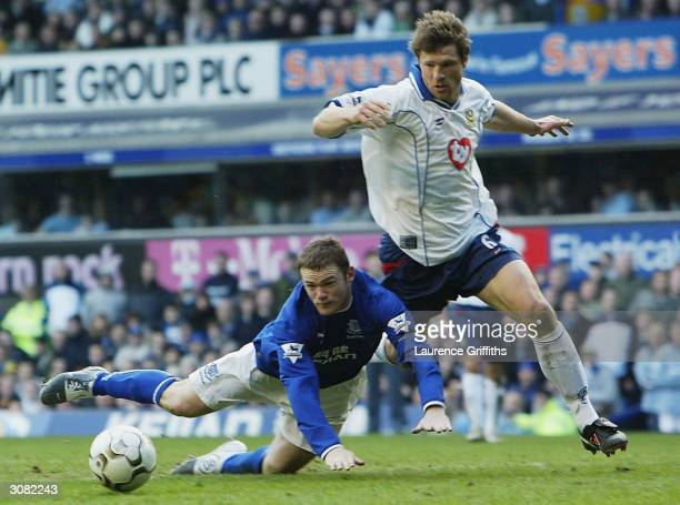 Wayne Rooney of Everton goes to ground under pressure from Arjan De Zeeuw of Portsmouth during the FA Barclaycard Premiership match between Everton...