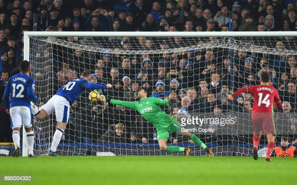 Wayne Rooney of Everton scores their third goal from the penalty psot past goalkeeper Lukasz Fabianski of Swansea City during the Premier League...
