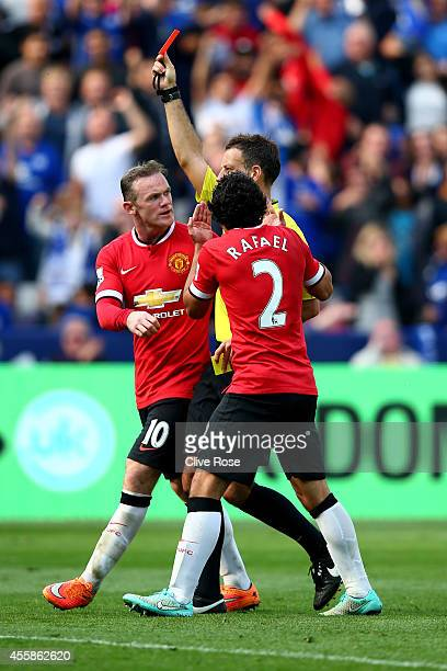 Wayne Rooney of Manchester United and Rafael of Manchester United protest as Referee Mark Clattenburg shows the red card to Tyler Blackett of...