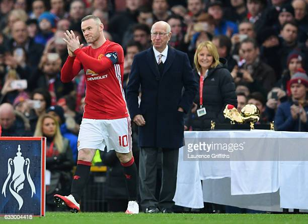 Wayne Rooney of Manchester United applauds the crowd scores as he is presented with an award for becoming the club's top goal scorer of all time from...