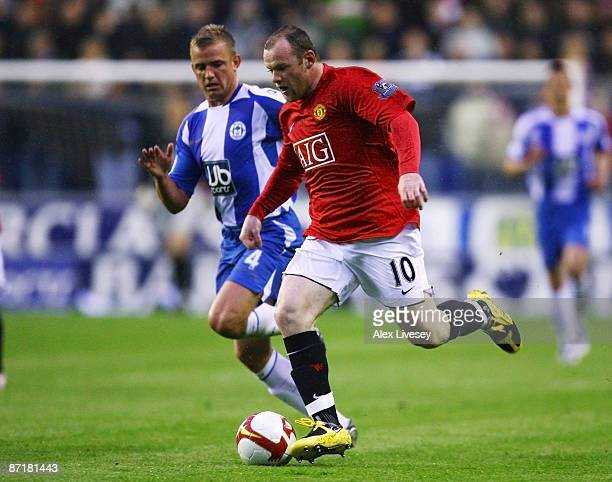 Wayne Rooney of Manchester United beats Lee Cattermole of Wigan Athletic during the Barclays Premier League match between Wigan Athletic and...