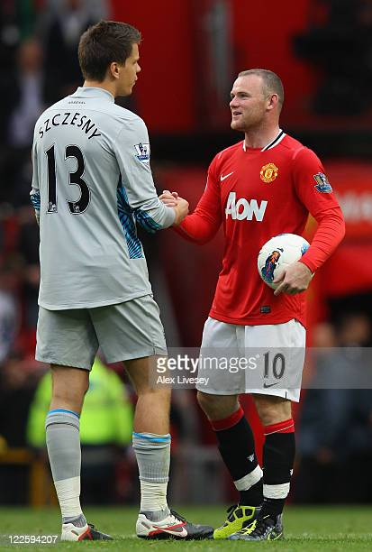 Wayne Rooney of Manchester United carries the match ball as he shakes hands with Wojciech Szczesny of Arsenal after the Barclays Premier League match...