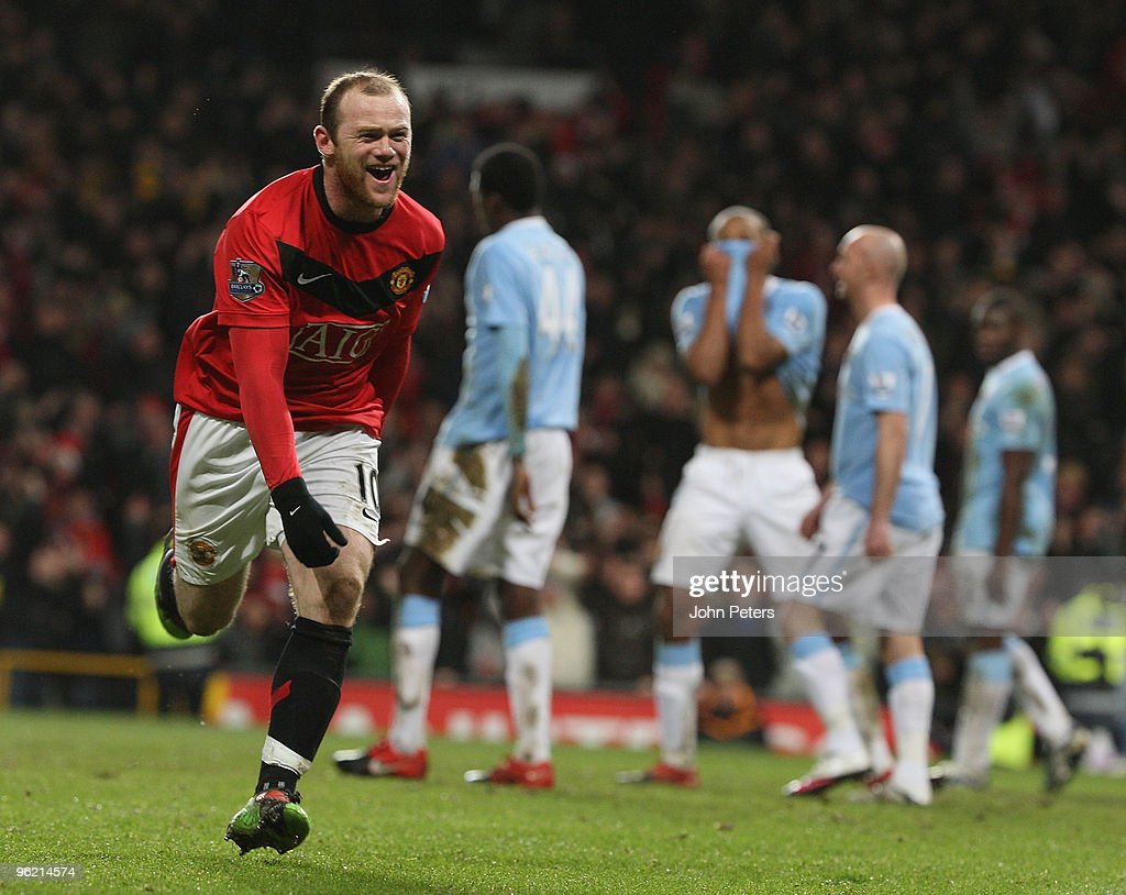 Wayne Rooney of Manchester United celebrates Michael Carrick scoring their second goal during the Carling Cup Semi-Final Second Leg match between Manchester United and Manchester City at Old Trafford on January 27 2010 in Manchester, England.